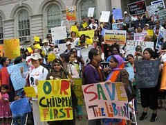 A group of people stand in front of a NY public library holding up signs in protest of library cuts. The signs in front of the crowd say 'Save our Library' and 'Our Children First'