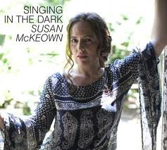 Susan McKeown, a white woman, wears a printed dress and looks at the camera. Her album cover reads Singing in the Dark in dark text