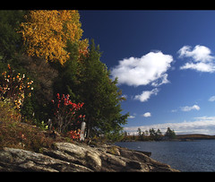 Kennisis Lake in Fall (robert_goulet) Tags: blue autumn trees red sky lake ontario canada colour fall water leaves yellow clouds corner point rocks rocky olympus changing deciduous zuiko exposed haliburton evolt e500 zd fourthirds 1454mm kennisis mikecrough