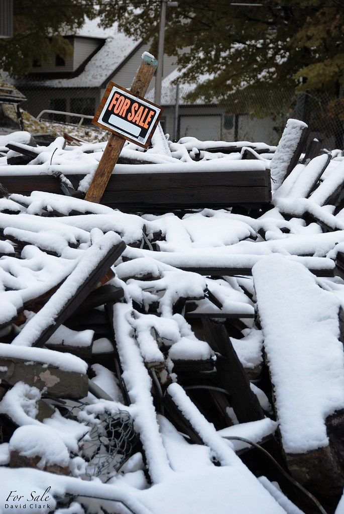 A for sale sign stuck in a huge pile of wrecked timber.