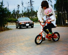 IMG_003484ps.JPG (Loops666) Tags: trees woman canada brick film girl bike bicycle newfoundland mom star kid child kodak sister 110 driveway bmw predigital 325i 1990s 90s 3series kodakstar110