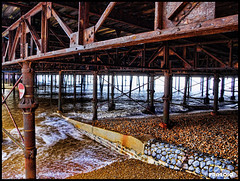 under the pier (Paul Adames Noble) Tags: ocean old uk red sea signs colour building beach broken metal architecture contrast warning rust waves stones vibrant olympus pebbles erosion windswept southofengland rails walkways hastings seafront crisscross eastsussex hdr weatherd e520 uksuncolour