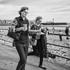Scarborough 02 (Peter.Bartlett) Tags: topazbweffects ricohgr noiretblanc fastfood tourists unitedkingdom people streetphotography urbanarte sea yorkshire lunaphoto walking girl square monochrome uk urban woman bag bw candid peterbartlett blackandwhite cardboardcup fence