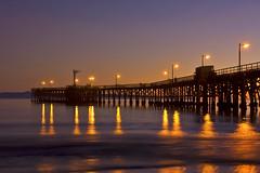 Here comes the night (Damian Gadal) Tags: ocean california longexposure sunset beach silhouette lights pier nikon waves pacific january nikond100 d100 2009 goleta