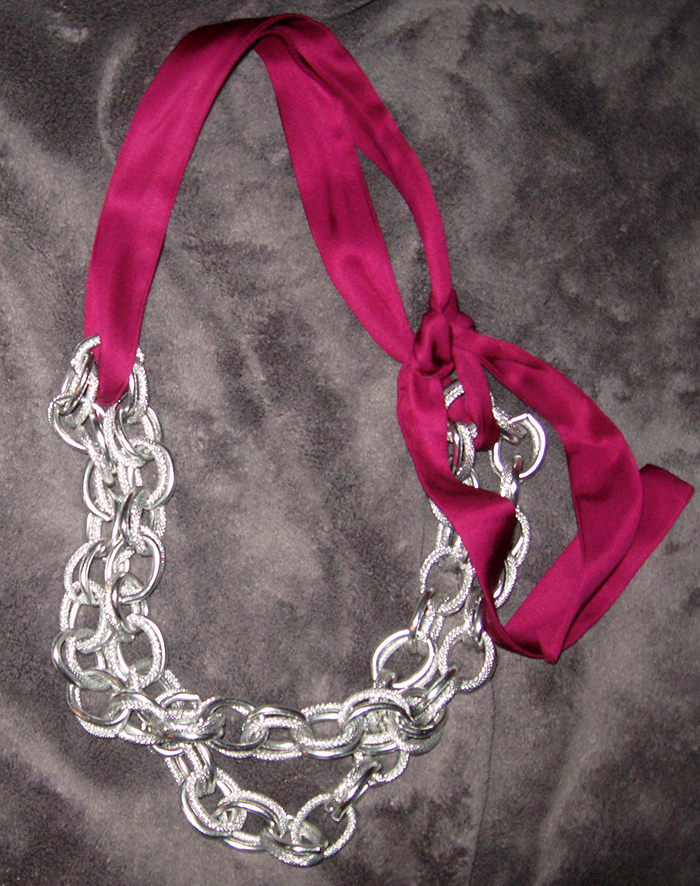chain necklace doubled with berry satin sash