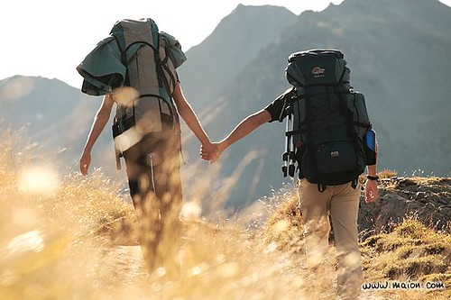 Backpackers couple walking hand in hand (Maurienne, French Alps, France, Europe)