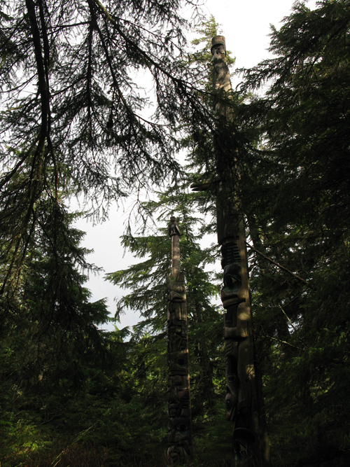 a peek at totems of Kasaan Totem Park through trees, Kasaan, Alaska