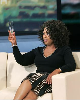 Oprah raising a glass of champagne on her television show