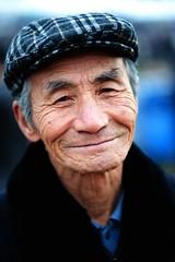 still a smile (Derekwin) Tags: old man smile hat zeiss asian nikon korea korean jeju wrinkles zf flickrduel d700 zeisszf  nikond700 makroplanar1002zf  100mmf2zfmakro