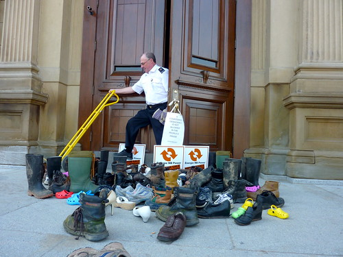 A commissionnaire at the Legislature struggles to open the front door that is blocked with a collection of shoes and boots.