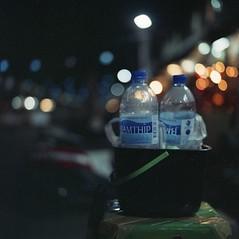 scumbag blues (hurtingbombz) Tags: stilllife 120 6x6 night thailand bucket market bokeh bangkok bronica pro mf f28 waterbottles 80mm suanlum sqai 800z zenzanon ps80