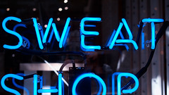 Partial sweat shop (Eric Flexyourhead) Tags: vancouver canada britishcolumbia bc gastown city urban detail fragment shop store kitandace window sign neon neonsign blue interpretation 169 olympusem5 panasoniclumix20mmf17