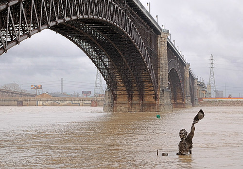 Riverfront in Saint Louis, Missouri, USA - bronze sculpture Captain's Return and Eads Bridge at high water