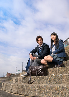 High school student couple sitting on stairs at beach
