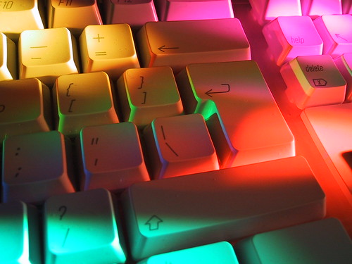 A computer keyboard with different coloured light shining on it