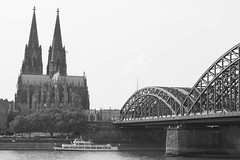 Cologne Cathedral (Kölner Dom) & Hohenzollern Bridge (Hohenzollernbrücke), Cologne, Germany. (Downtime_1882) Tags: horizontal landscape outdoors europe famous famousplace bw blackandwhite blackwhite blackwhiteimage bwimage blackandwhiteimage köln cologne germany deutschland federalrepublicofgermany bundesrepublikdeutschland building buildingexterior buildingexteriors buildings architectural architecture sky colognecathedral kölner dom kölnerdom hohenzollernbridge bridge river water hohenzollernbrücke boat riverrhine therhine rhine rhineriver touristdestination touristdestinations travel traveldestination traveldestinations canonef2470mmf28liiusm canoneos7d canoneos eos7d 7d canon