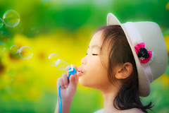 Asian little girl is blowing a soap bubbles in sunflower garden (anekphoto) Tags: park light summer portrait sun game cute green nature girl beautiful face grass childhood smiling yellow female season asian fun outdoors happy person kid spring soap healthy funny pretty child play little joy innocent daughter young meadow happiness bubbles blowing blow human thai sunflower leisure positive lovely sunbeam caucasian