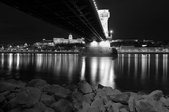 under the bridge (JavierVazquez) Tags: old city travel bridge blue light urban bw cloud reflection tower castle history tourism horizontal stone skyline architecture night river europe hungary european cityscape exterior view traffic capital budapest culture parliament scene palace tourist panoramic structure illuminated chain transportation frame magyar danube built municipal imagery hungarian destinations nobility