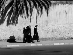 Stepping out (halifaxlight) Tags: street shadow bw wall contrast walking women child morocco palmtree medina meknes blinkagain