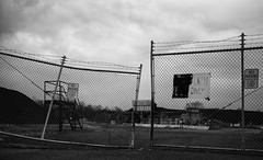 Industrial Blight (Dalliance with Light (Andy Farmer)) Tags: factory abandoned landscape decay industrial barbedwire gate bw ruin asphalt fence southbrunswicktownship newjersey unitedstates us