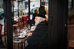 Par la vitrine d'un café dans la Rue du Dragon..Le dragon est en cage.. (Paolo Pizzimenti) Tags: femmemode homme dragon vitrine élégance barbe casque paris paolo olympus zuiko penf 25mm f18 film pellicule argentique m43 mirrorless doisneau