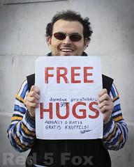 Free Hugs (Red 5 Fox) Tags: man writing mouth hair paper glasses words hands teeth text trafalgar trafalgarsquare free shades curly jumper hugs stuble freehugs