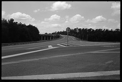 Bridge Approach (FreezerOfPhotons) Tags: leicam4p jupiter850mmf2 kmz fujifilmneopanacros100 legacyprofujifilmneopanacros100 xtol concrete road lines paint metal sign trees sky