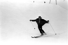 04a3971 39 (ndpa / s. lundeen, archivist) Tags: nick dewolf nickdewolf bw blackwhite photographbynickdewolf film monochrome blackandwhite candid streetphotography april 1971 1970s 35mm austria stanton stantonamarlberg alps tyroleanalps tyrol mountains snow snowcovered slopes skiing skitrip skislopes skiresort people man youngman skier cape tirol alpine skis poles skipoles