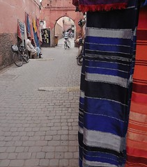Moroccan textiles for sale (SM Tham) Tags: africa morocco marrakech theredcity oldmedina walledcity unescoworldheritagesite streetscene street lane cloths textiles rugs streetvendors merchants