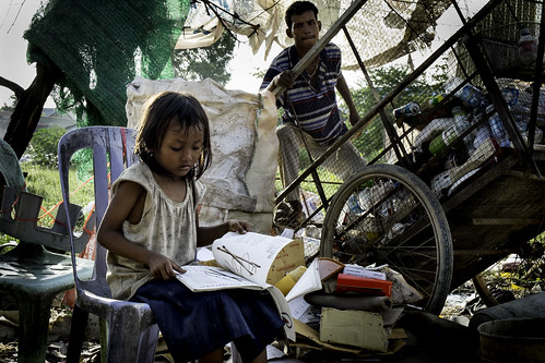 a girl with a book in dump area of Phnom Penh