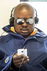 Distracted 18 (World of Tim) Tags: distracted people public transport east london line black man mobile phone using sunglasses overground underground march 2017 game headphonesbald canon s120 compact digital camera tim saunders photo photographer photography available existing ambient light train reflection uk gb britain england united kingdom great