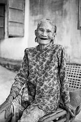 Smiling lady (pacco_racco) Tags: lady old smile portrait wall texture hoian vietnam blackwhite leicam6 leicasummicron35mmf20asph kodaktrix400