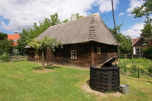 Chałupa (1784) ze wsi Kopojno w skansenie w Gosławicach od strony studni