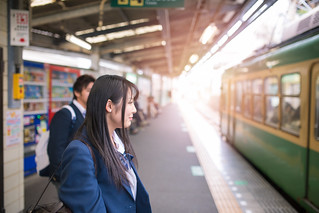 High school girl waiting for train on platform