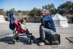 mother and daughter (dominic_wenger) Tags: greece sindos thessaloniki athen frakapor refugee refugees refugeecamp camp military crysis borders open world problem swisscross volunter help portrait face family poor man woman kids chil child children beautiful beauty war syria tent tents hall light dark cold candid looking people human humanity sun boring life flee volunteer frame sigma35 sigma canon 5dmk3 lowlight sigmaart mother daughter buggy small babx baby smart cute smile sunshine blue sky warm shaddow macedoniagreece makedonia