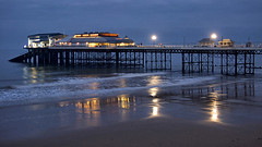 Cromer Pier Dusk (lincoln_eye) Tags: uk sea england beach clouds buildings reflections pier seaside spring twilight waves unitedkingdom dusk streetlights may overcast structure foam gb cromer lampposts northnorfolk