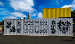 The Cosmic Container (Steve Taylor (Photography)) Tags: cat skateboard surfboard bird rose flower teeth art design graffiti mural streetart shop store blue black white yellow metal container newzealand nz southisland canterbury christchurch city corrugated sky cloud sunny