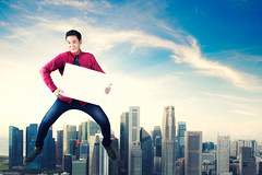 Happy man jumping with holding blank paper  cityscape in the background (Krunja) Tags: abstract action active advertise asian background banner blank board business cheerful child city concept copyspace effect energy fashion freedom fun guy happiness happy holding jeans joy joyful jumping kid lifestyle male man motion neck newyork outdoor paper particle people person playful playing portrait showing sign smile sporty success successful teen teenage teenager urban white whiteboard young