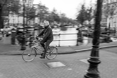 Biking on the canal (livio.luca) Tags: amsterdam bike streetphotography street panning bw blackandwhite velocity canal europe