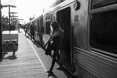 stepping out (KevinIrvineChi) Tags: cta chicagoist chicago ctabrownline kedzie albanypark commuters passengers train tracks transit platform trainplatform railroad rail sunny backlit sun vanishing points illinois consumerist sony dscrx100 sweater jacket sandals woman backlighting