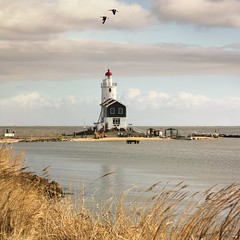 The lighthouse of Marken for many years an iconic landmark (Bn) Tags: sea summer dykes lighthouse holland green heritage history water netherlands dutch grass landscape island boat site topf50 day cows flat cloudy tourist canals unesco national level pastures below summertime recreation former dijk peninsula topf100 dike marken tabouret authentic ijsselmeer weiland waterland koe koeien noord nominated polders 100faves 50faves rijksmonument gouwzee paardvanmarken oosterpad vuurwachter