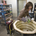 Summer Zickefoose putting clay in the kiln to be fired.