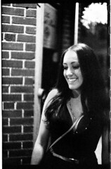 LindseyM6SummitarDelta_089 (Johnny Martyr) Tags: darkhair darkhairedgirl woman smile teeth whiteteethanddarkhair purse straps hot lookdown glancedown smilingandlookingdown happy bar drunk drinking barhoping barhopping bw philly philadelphia brick portrait candid photojournalism documentary beautifulgirl gorgeousgirl exotic exoticbeauty style stylish stylishbrunette perfectjawline beautifulchin standing talking laughing leica leitz leitzsummarit 50mm 35mm film grainy grain ilforddelta6400 blackandwhite contrast street streetlightatnight girlinthestreetlight girlinphillystreetlight gracefulslopingchin graceful sloping jaw presence gracefulslopingjaw eyelids eyeliner darkness shadows streetportrait girloutsideofabar womanoutsideofabar outsidethebar womanoutsidethebar tinywaist plungingneckline lowcuttop necklace pursestrap