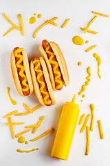 Mustard bottle and hot dogs (foodio) Tags: hot dog mustard french fat obesity fries fried potatoes food sauce bottle plastic american street traditional yummy delicious meal tasty appetizing light background top view teen kid hunger fast nutrient calorie meat sausage manufactured bread flour recipe snack protein spicy bite western unhealthy weight preference diet intake dinner lunch lifestyle
