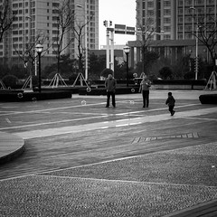 Bubble breaker (Go-tea 郭天) Tags: kid boy child young guy bubbles soap air fun funny enjoy enjoying play playing square building run running fly flying trees man woman family together love grandma grandpa granny grandfather grandmother grandchild grandson 3 cold day coats loo looking watch watching glasses canon eos 100d 50mm prime street urban city outside outdoor people bw bnw black white blackwhite blackandwhite monochrome naturallight natural light asia asian china chinese shandong afternoon out entertainment cool