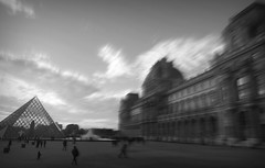 Crossing the courtyard (Bjrn Giesenbauer) Tags: sky bw paris france museum architecture clouds pyramid louvre
