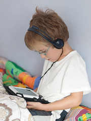 Little boy using tablet with earphones on the bed (Carlos Ciudad - Stock Photography) Tags: old light portrait espaa luz home childhood vertical wall digital children pared 50mm glasses casa pc bed spain hands europa europe sitting technology child natural retrato 4 watch olympus manos peliculas indoors leon blanket blonde sentado headphones movies gafas years cama tablet infancia nio zuiko manta earphones gettyimages ver tecnologia auriculares aos rubio cascos castillayleon tableta e520 castilleandleon gettyimagesspain cctrillastock