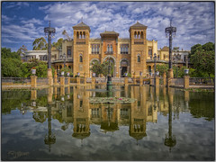 Reflejos de Sevilla I. (Capuchinox) Tags: seville sevilla spain españa hdr photomatix reflejos agua water estanque plaza square cielo nubes sky clouds andalucia andalusia arquitectura building reflejo reflection olympus pond nik