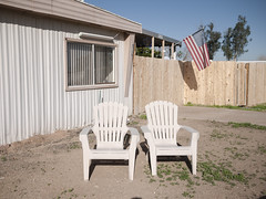 West of 27th Avenue (GC_Dean) Tags: street city arizona urban color colors phoenix chair flora cityscape colours shadows chairs space flag sunny americanflag structure trailer trailerpark mobilehome mundane emptiness sunnyday twochairs hardlight sociallandscape