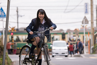 High school girl riding bicycle near station
